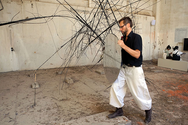 Nikolaus Gansterer, Sympoiesis Obersatory, 2019, performance at site specific installation with found materials, mirrors, bamboo, wood, wire, sound, video, 14th Sharjah Biennial, Ice Factory, Kalba, UAE